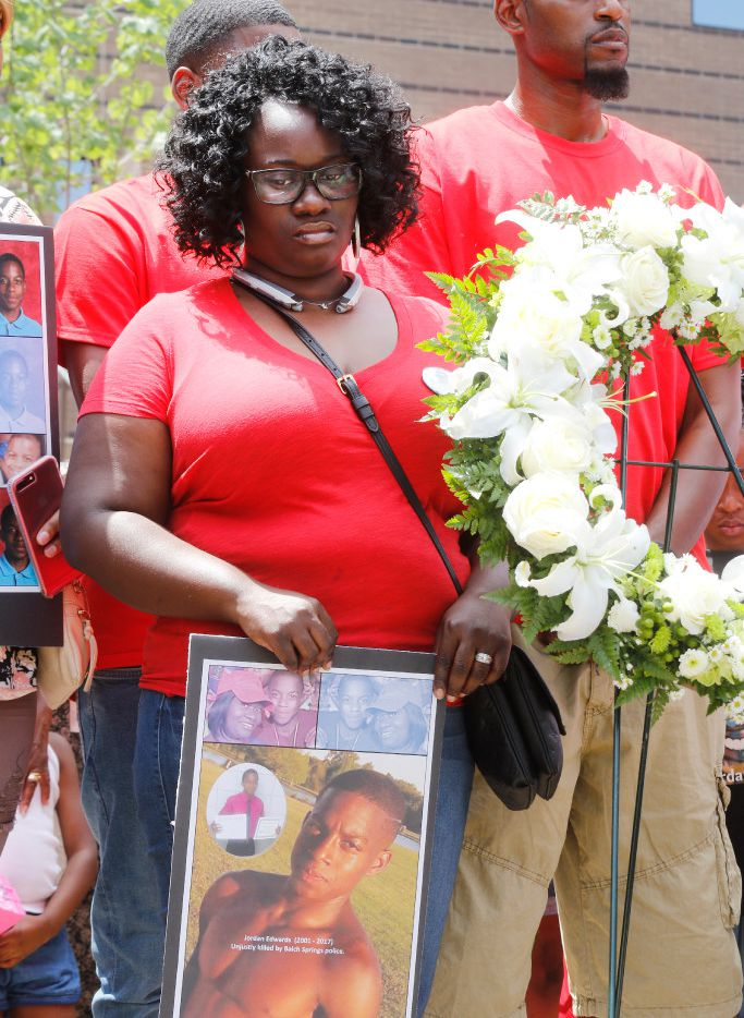 Charmaine Edwards and her husband, Odell Edwards, stand by a wreath placed on the steps of the Frank Crowley Courts Building during a rally Saturday remembering Jordan and others killed by police.