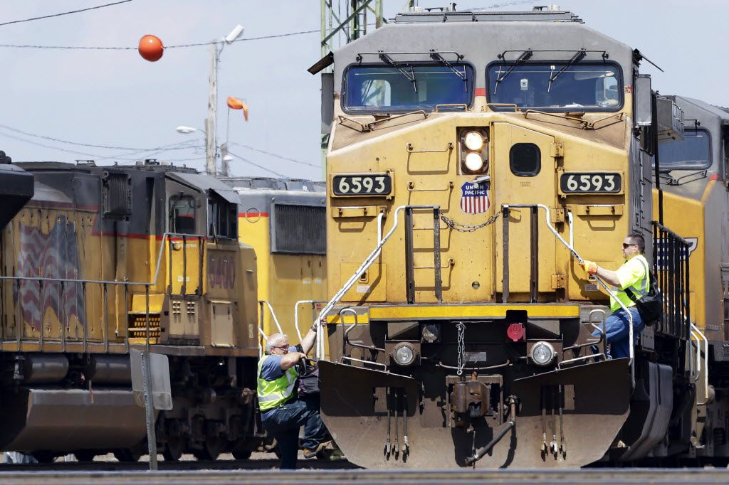 A train operator (left) dismounts a Union Pacific locomotive while another operator climbs up at a railyard in Council Bluffs, Iowa.