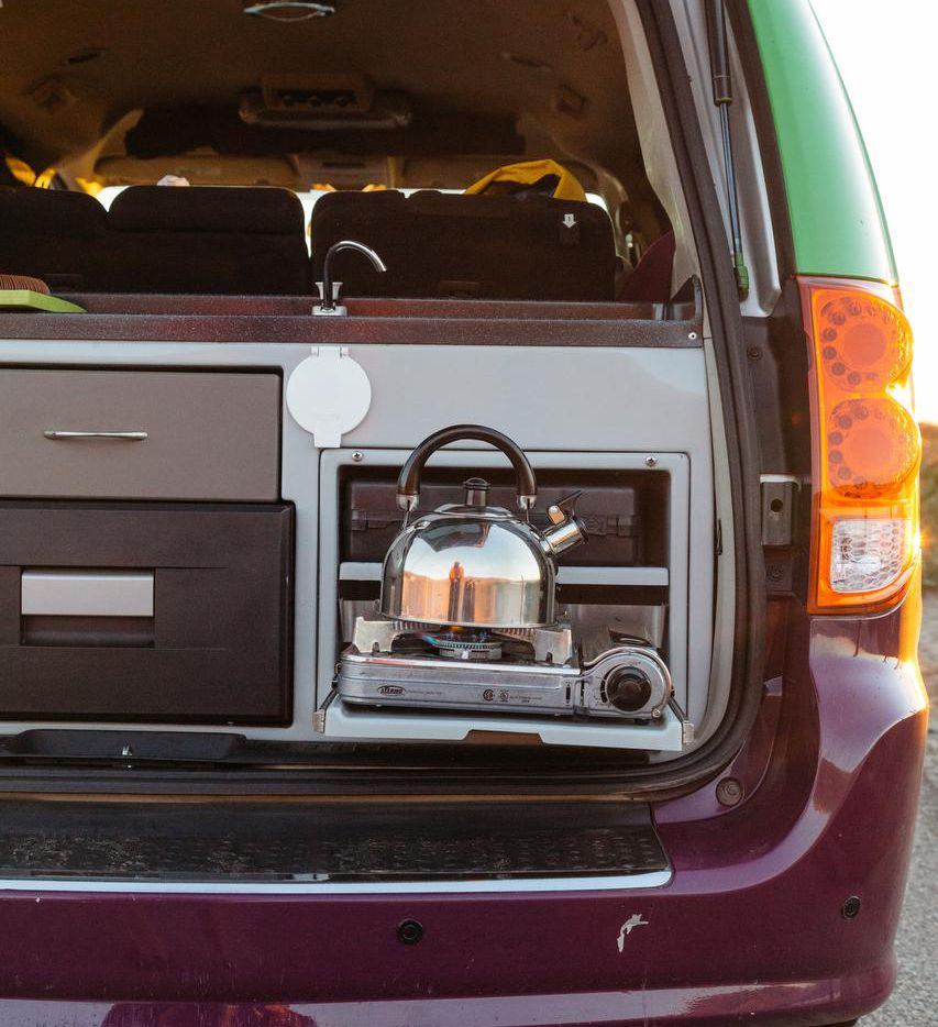 A kettle of water  warms up over the van's propane burner.