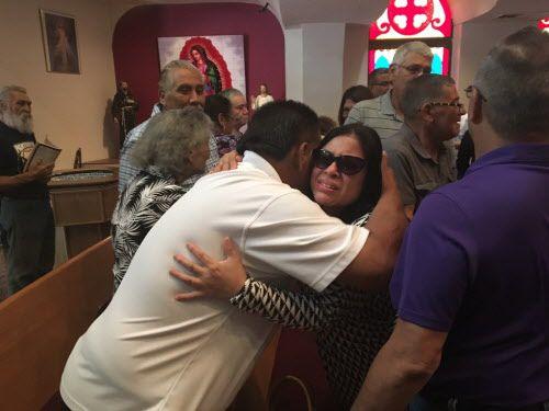 Héctor Zamarripa, tío del agente Patrick Zamarripa, abraza a otros miembros de su familia durante una misa el domingo en la mañana en la iglesia All Saints Catholic Church de Fort Worth. (Caleb Downs/ DMN)