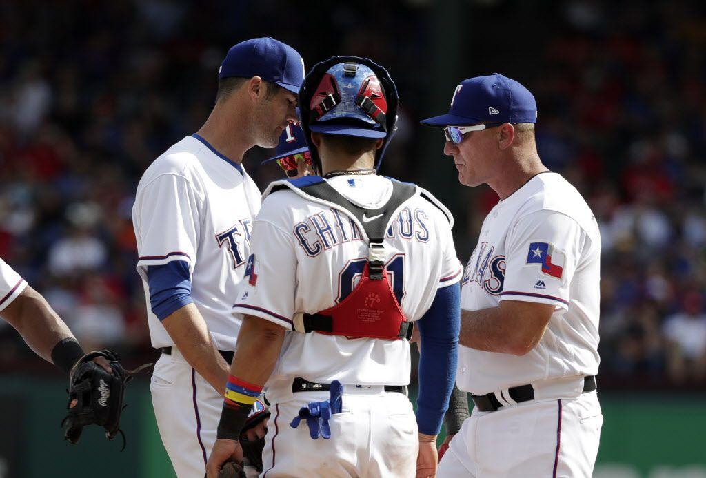 Cole Hamels (izq.) habla con el mánager de los Rangers, Jeff Banister. (AP Photo/Tony Gutierrez)