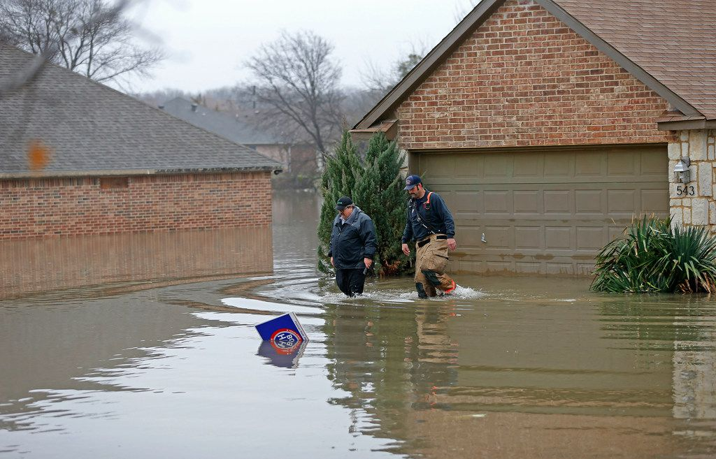 Rodger Williams, left, leaves his flooded house with a Rockwall firefighter on Lakeside Drive in Rockwall, Texas, Thursday, Feb. 22, 2018.