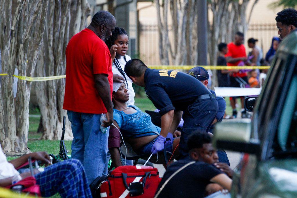 A Dallas Fire-Rescue paramedic checks out a woman that fainted at the scene of a shooting at the Roseland Town Homes that left a 9-year-old girl dead.