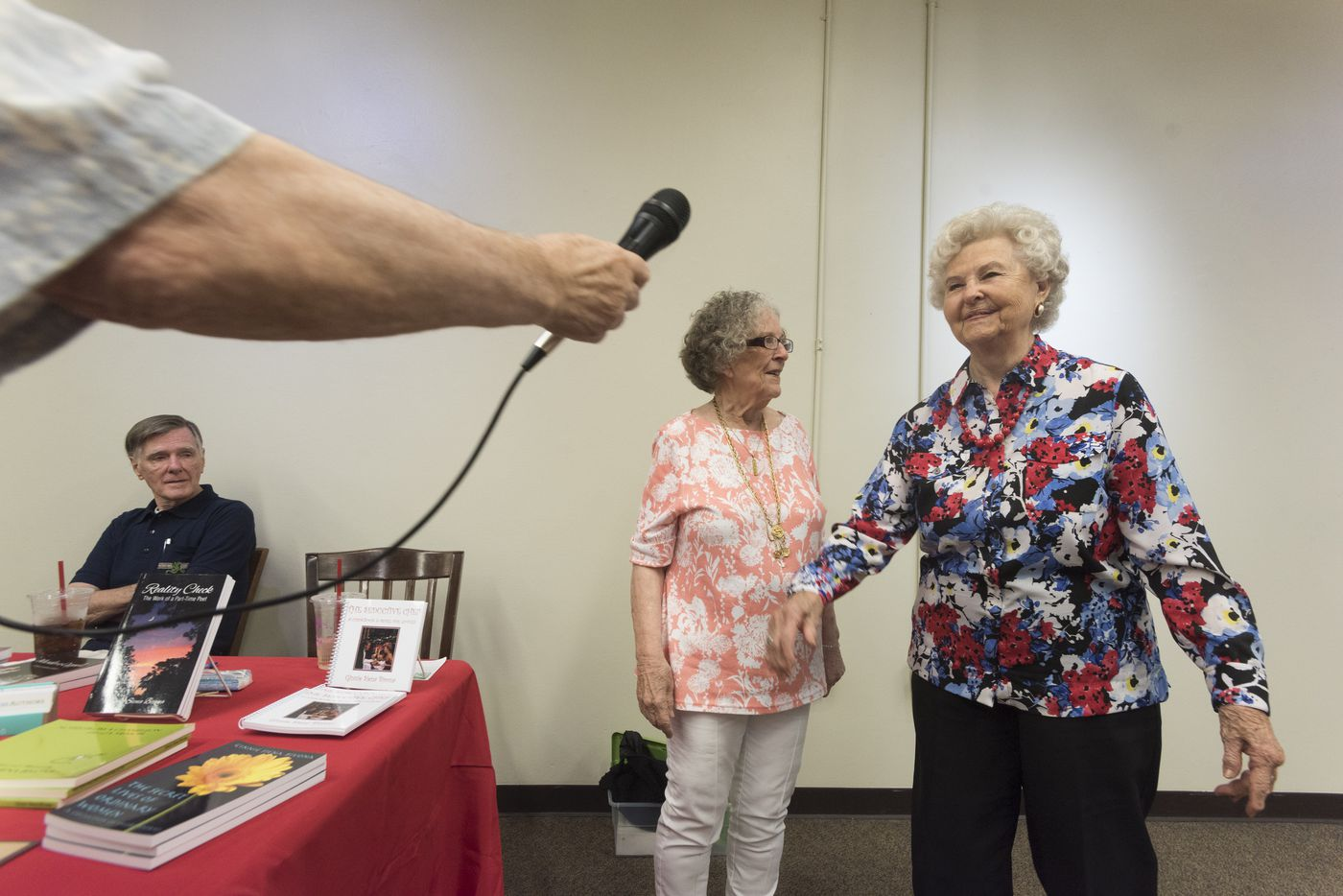 Larry Upshaw hands Barbara Mott, 92, a microphone so she can talk about how she became an author at 82 during a book signing event at Half Price Books on Sunday, June 26, 2016.  Upshot and Ginnie Siena Bivona, center, have launched Ageless Authors, a publishing project for people 65 and older.   (Rex C. Curry/Special Contributor)
