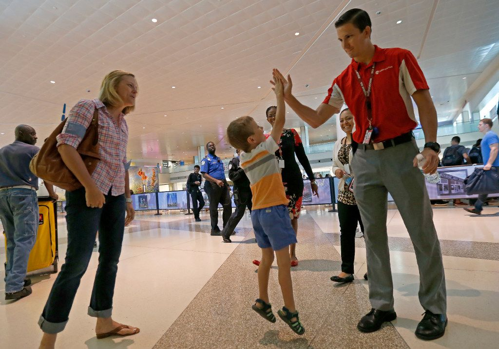 """Luke Swofford (second from left), 4, high fives Ian Fryers (right), Airport Security Compliance Officer, who found Luke's teddy bear named """"Teddy Bear,"""" on the way to pick up his beloved Teddy Bear as Luke's mother Nikki Swofford looks on at Dallas Love Field Airport."""