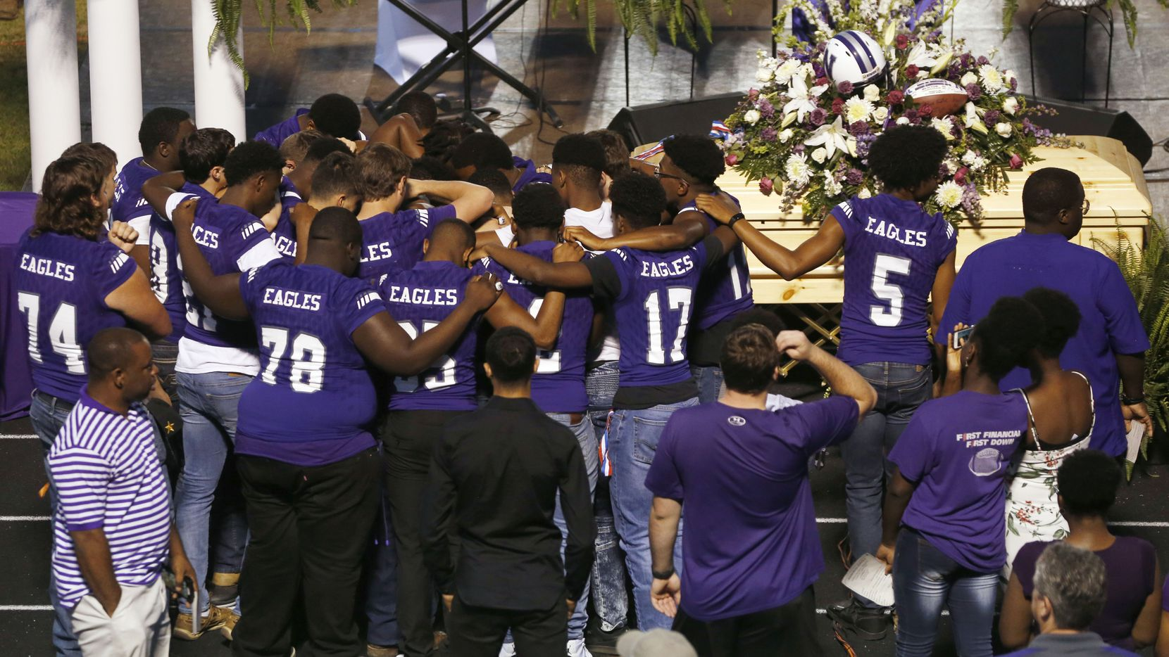 """Newton High School football team talk to each other after a memorial service for Newton High School head football coach William Theodore """"W.T."""" Johnston at Curtis Barbay Field at Newton High School in Newton, Texas on Wednesday, May 15, 2019. (Vernon Bryant/The Dallas Morning News)"""