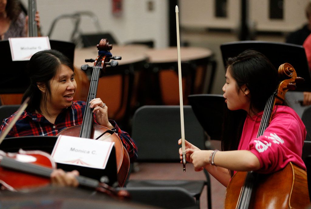 Monica Chi gets some instructional help from her daughter Julianne Chi, 14, during a practice for parents of students at Liberty High School in Frisco on Nov. 7.