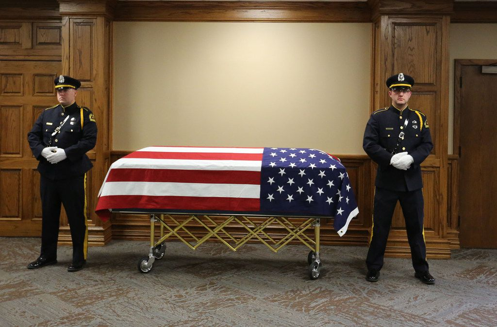 An honor guard stays with the body of Officer Rogelio Santander at Lake Pointe Church in Rockwall before his funeral.