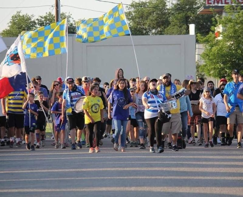 Fort Worth Vaqueros fans march to a match.