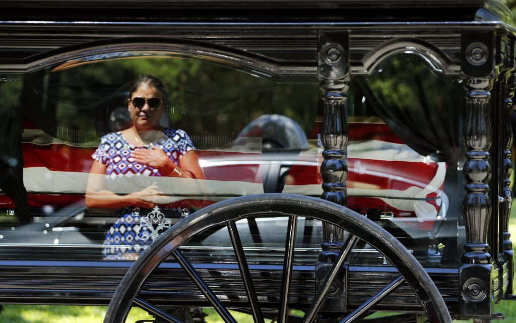 In the reflection of the horse-drawn caisson, a Smith family member places her hand over her heart as she pays her respects to Dallas police Sgt. Michael Smith as he was laid to rest at the Restland Funeral Home and Cemetery in Dallas, Thursday, July 14, 2016. Smith was gunned down in an ambush attack in downtown Dallas a week ago. Four Dallas police officers and one DART officer were killed. (Tom Fox/The Dallas Morning News)