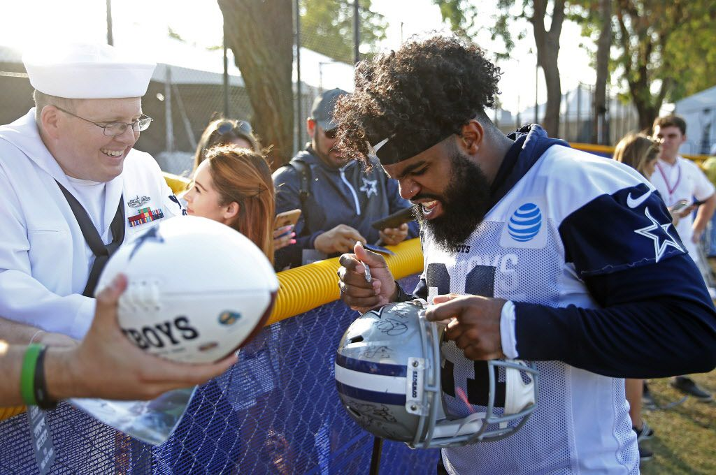 Dallas Cowboys running back Ezekiel Elliott, right, signs autographs for Christopher Smith after afternoon practice at the training camp in Oxnard, Calif., Friday, July 27, 2018. (Jae S. Lee/The Dallas Morning News)
