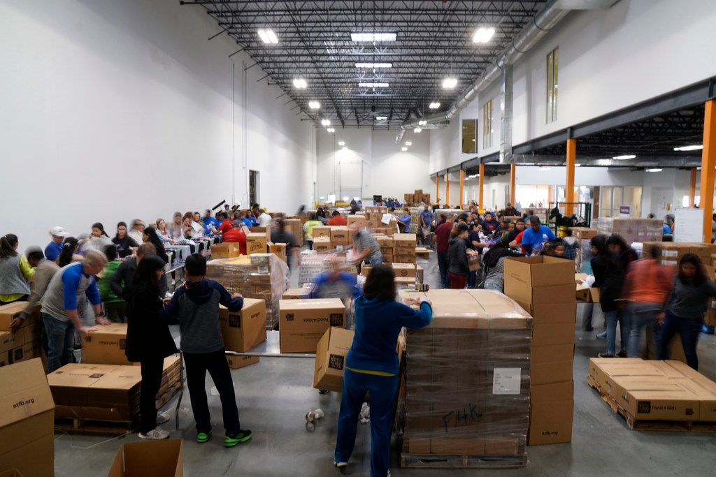 Volunteers box up everything from vegetables to cookies for families in need during a volunteer shift of the Indian American Council at the North Texas Food Bank in Plano.  (Lawrence Jenkins/Special Contributor)
