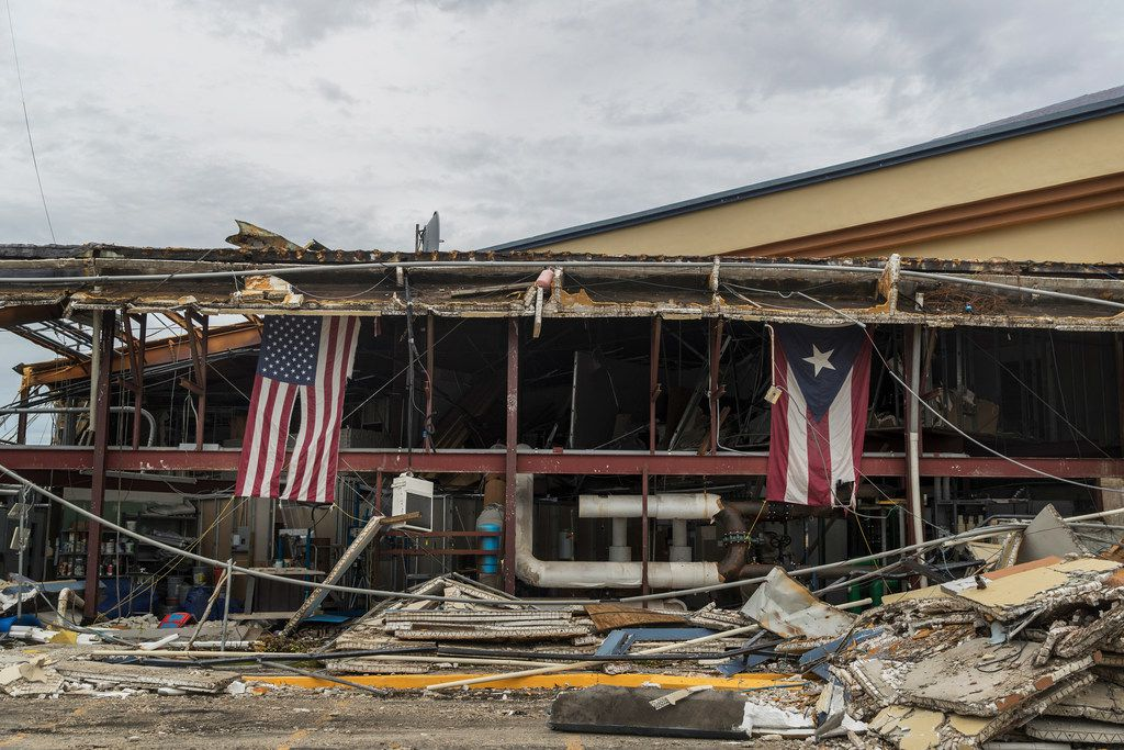 American and Puerto Rican flags hang from a church heavily damaged by Hurricane Maria in Carolina, Puerto Rico. A surge of fuel and food supplies and federal government personnel has begun to arrive in Puerto Rico, the governor of the storm-battered U.S. territory said Sunday morning. (Victor J. Blue/The New York Times)