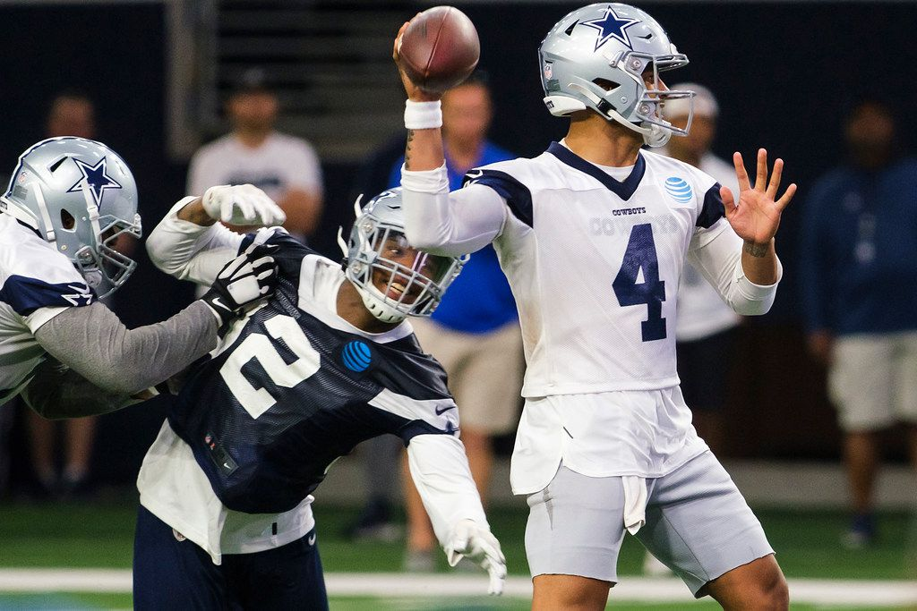 Dallas Cowboys quarterback Dak Prescott (4) throws a pass under pressure from defensive end Dorance Armstrong (92) during a team OTA practice at The Star on Wednesday, June 5, 2019, in Frisco. (Smiley N. Pool/The Dallas Morning News)