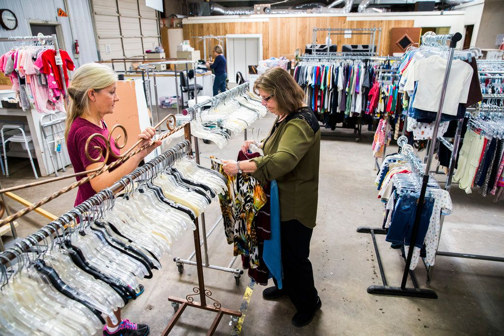 Director Gayle Schielack (left) talks to volunteer Maxine Ballard while sorting clothing at Second Chance Emporium in La Grange. The nonprofit store provided clothing and supplies for flood victims for the entire month of September, after losing their own building.