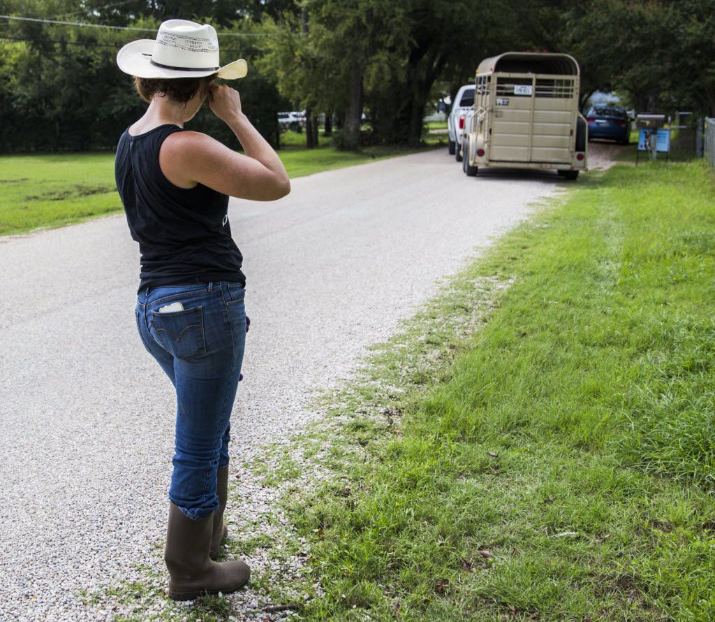 Jess Anselment wipes away a tear as Elizabeth Hendel of Royce City, Texas drives away with two adopted donkeys.