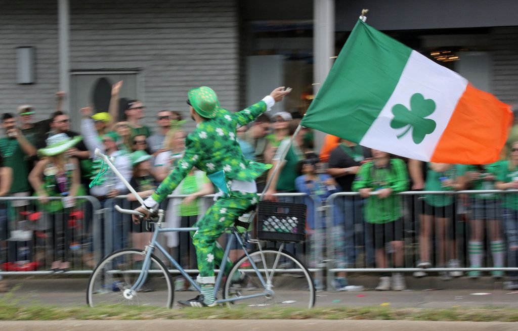 A bicyclist speeds down the parade route during the Dallas St. Patrick's Parade & Festival along Greenville Avenue in Dallas on Saturday.