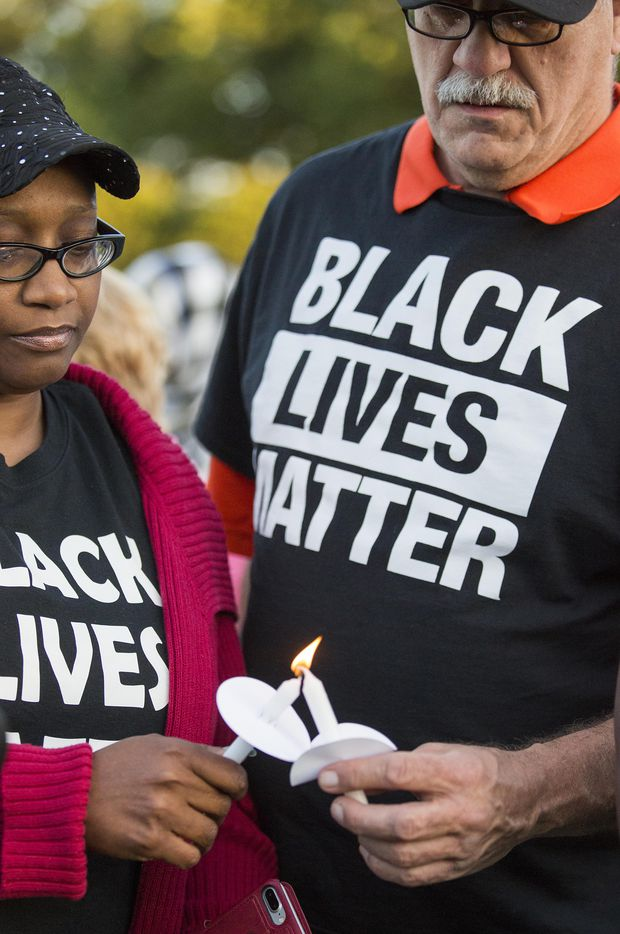 """Monica Tunstle-Garrett (left) helps Al Woolum light a candle during the """"Remember His Name: Vigil for Jordan Edwards"""" candlelight vigil at Virgil T. Irwin Park on Thursday, May 4, 2017, in Balch Springs, Texas."""