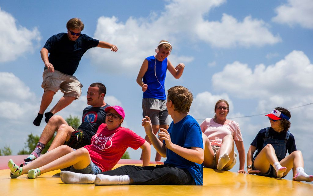 Jamie Wheeler-Matlock, second from right, Austen Wheeler,  third from left, and other autistic adults and aides jump on a giant jumping pillow at the Gentle Zoo.