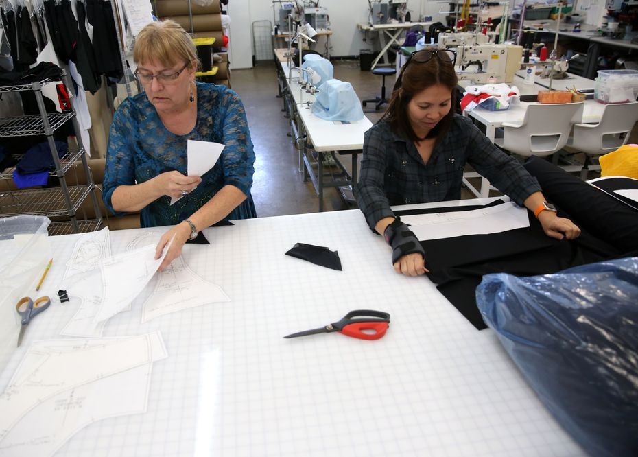 Merri Lester (left), product development engineer, and Ha Vo, sample maker, cut patterns for a prototype suit at the company's headquarters in Dallas. The Design District office includes workshops to make samples of apparel and sunglasses.