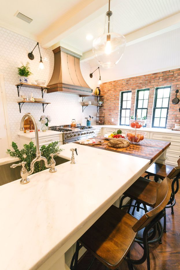 Tara Lenney eased the architecture toward a more Parisian style in this North Texas kitchen by using brick in the same color as the home's exterior to create the impression that the kitchen has always had an exposed brick wall.