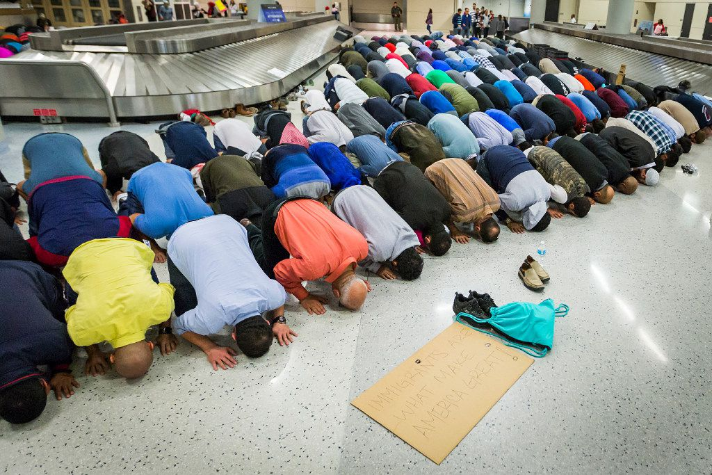 Muslim men set down their protest signs to pray at DFW International Airport where they gathered in opposition to President Donald Trump's executive order barring certain travelers on Sunday, Jan. 29, 2017.