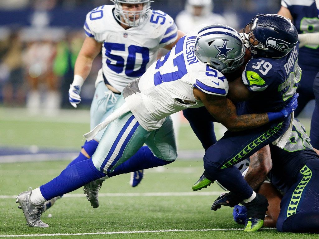 Dallas Cowboys outside linebacker Damien Wilson (57) tackles Seattle Seahawks running back Mike Davis (39) during the second half of play at AT&T Stadium in Arlington, Texas on Sunday, December 24, 2017. Dallas Cowboys lost to the Seattle Seahawks 21-12. (Vernon Bryant/The Dallas Morning News)