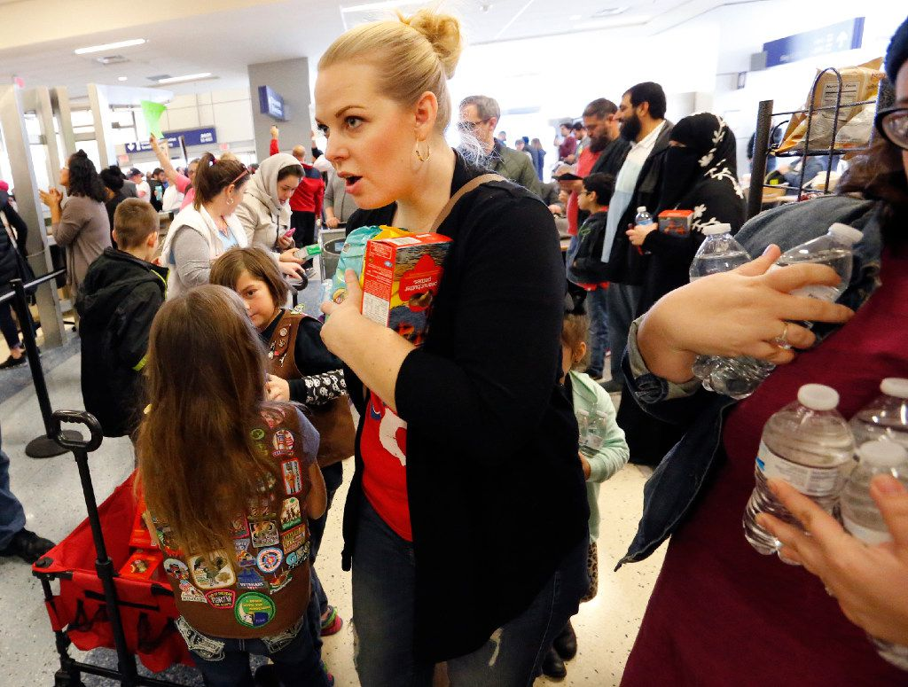 Jackie Spivey, leader of Troop 2724 in Haslet, Texas, helps distribute Girl Scout cookies and water to hungry protesters at the international arrivals gate in Terminal D at DFW Airport on Sunday, January 29, 2017. (Louis DeLuca/The Dallas Morning News)