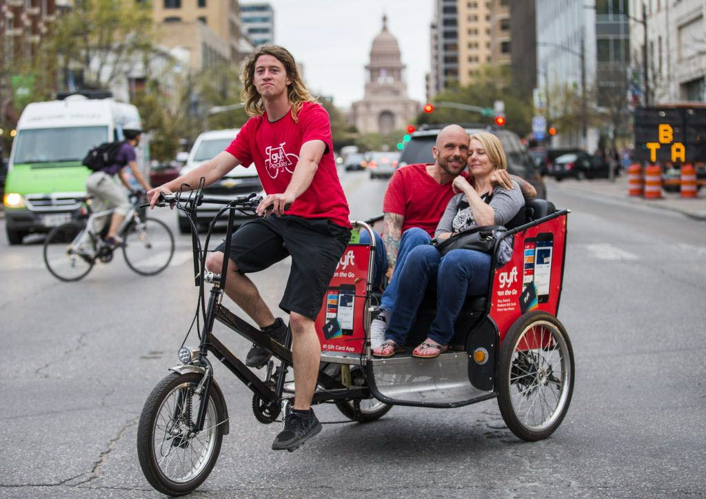 A pedicab driver transports a couple through the intersection of Congress Avenue and Fourth Street, in front of the Texas capitol during the 2015 SXSW interactive and film festival on Sunday, March 15 in downtown Austin.