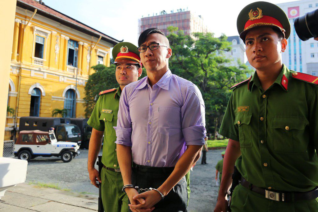 "Vietnamese police escorted American citizen William Nguyen to court July 20. Nguyen was deported Friday after being found guilty of ""disturbing public order"" during a peaceful protest June 10 in Ho Chi Minh City. (Agence France-Presse)"