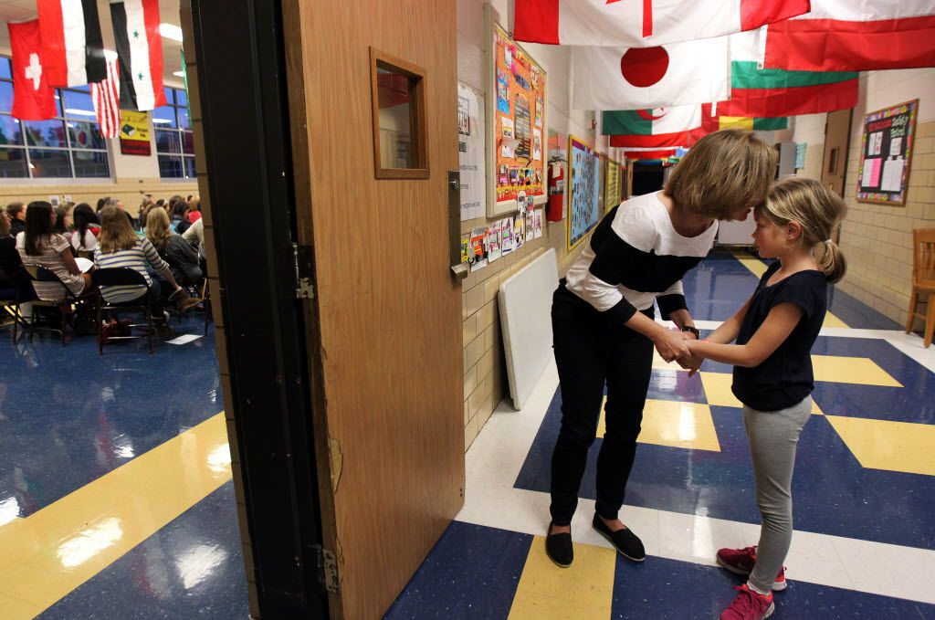 Richardson ISD hosted a meeting at White Rock Elementary School in Dallas Monday evening to address parental and community concerns over a proposal to add classrooms to alleviate over crowding and increasing enrollment.  Kathy Baumgarten spoke with her daughter, Ellie Baumgarten, 7, in the hallway before going into the meeting after her father, James Baumgarten, not pictured, dropped her off.  Ellie is a student at White Rock.  (Mona Reeder/The Dallas Morning News)