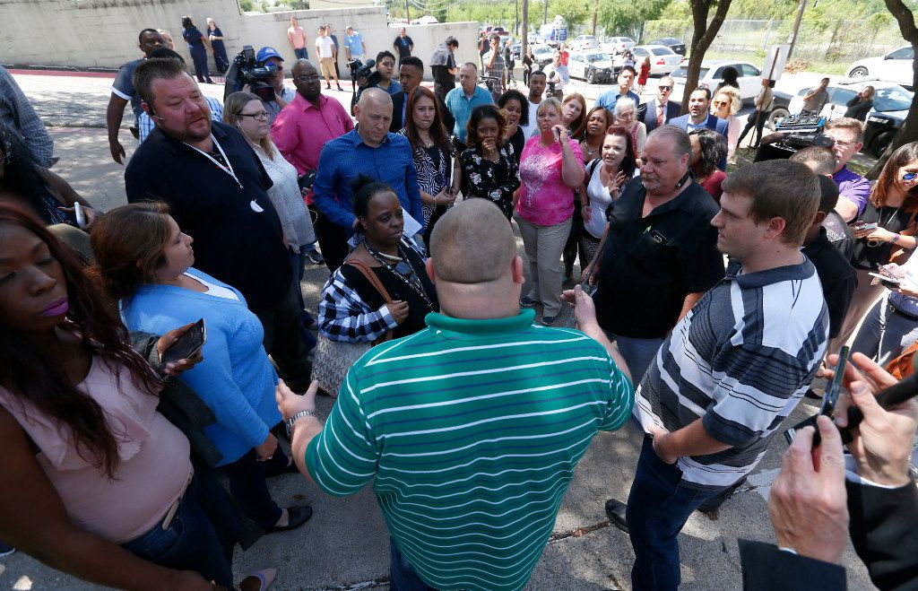 Chris Collinsworth (in a green stripe shirt) talks with his co-workers in the parking lot outside an office building in Lake Highlands near the High Five where police found two people dead inside the office building in Dallas, Monday, April 24, 2017. (Jae S. Lee/The Dallas Morning News)