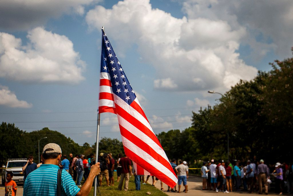 A resident of the Cinco Ranch Canyon Gate subdivision holds the American Flag during a demonstration at a police road clock outside their neighborhood on Saturday, Sept. 2, 2017, in Katy, Texas. The area remains cordoned off due to flood waters left by Hurricane Harvey.