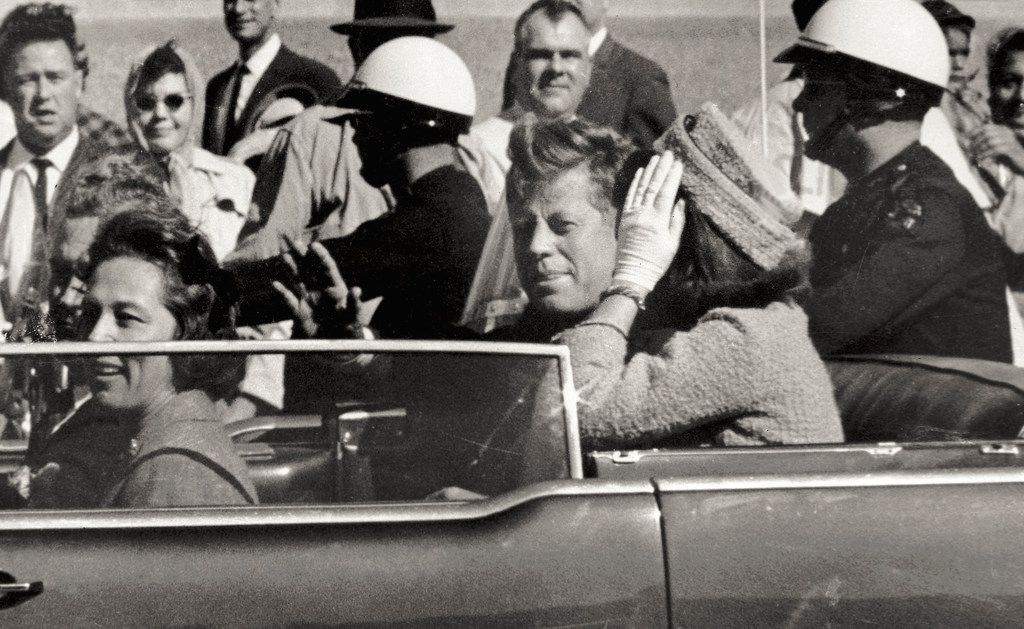 In this Nov. 22, 1963 photo, President John F. Kennedy waves from his car in a motorcade approximately one minute before he was shot in Dallas. Riding with Kennedy are First Lady Jacqueline Kennedy, right, Nellie Connally, second from left, and her husband, Texas Gov. John Connally, far left. (AP Photo/Jim Altgens, File)
