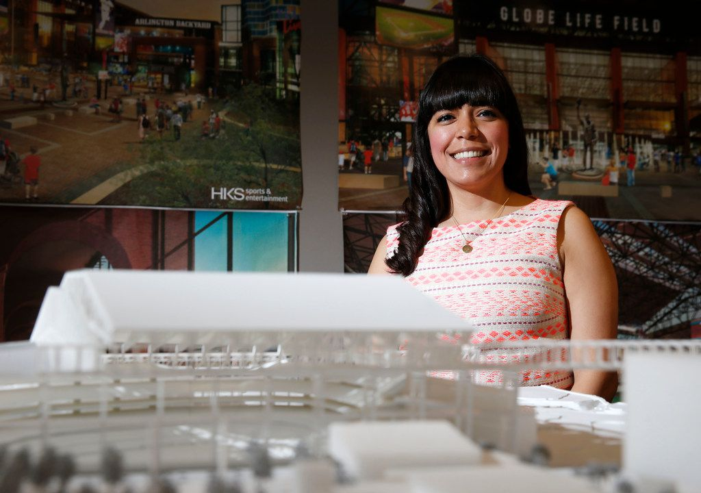 Aguirre poses for a portrait in front of a model of Globe Life Field near her desk at HKS.