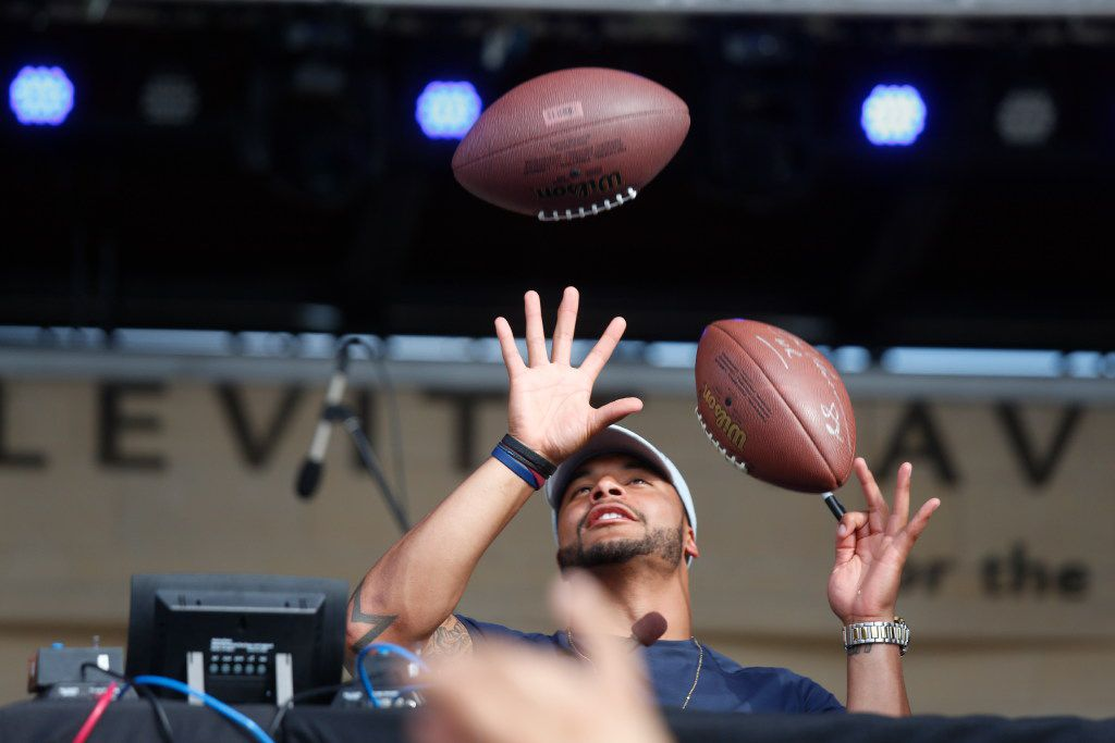 Dallas Cowboys quarterback Dak Prescott's tries to catch multiple footballs to sign during a commercial break during his appearance at Mudbug Bash 2017, held at the Levitt Pavillion on Arlington Saturday April 15, 2017. The promotional event was held for fans of 105.3 The Fan radio station. (Ron Baselice/The Dallas Morning News)