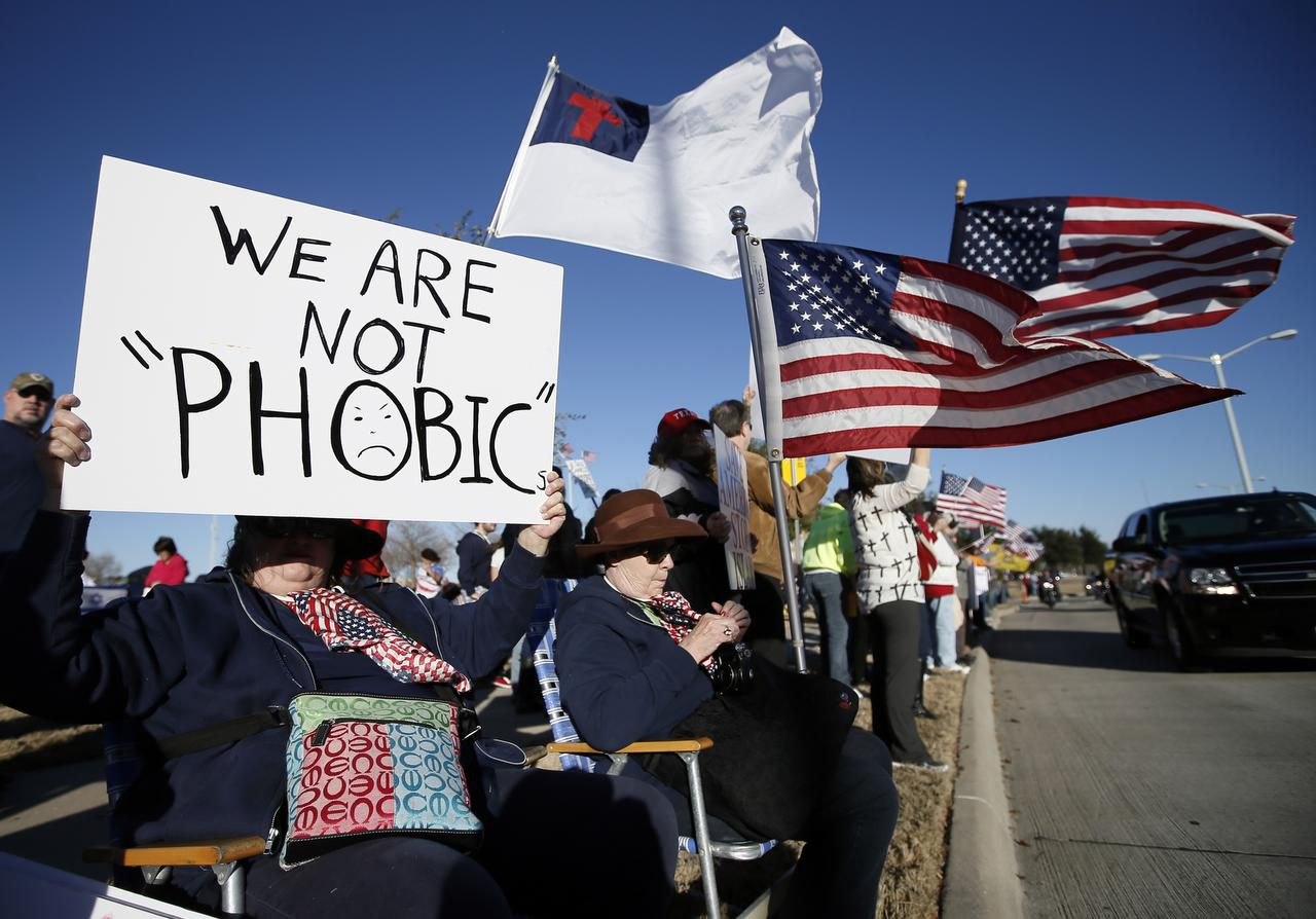 Annie Kobus of Dallas, holds a sign as she joins nearly a thousand other protestors outside the Curtis Culwell Center, Saturday, Jan. 17, 2015, in Garland, Texas. A muslim conference against terror and hate was scheduled at the event center. (AP Photo/Tony Gutierrez)