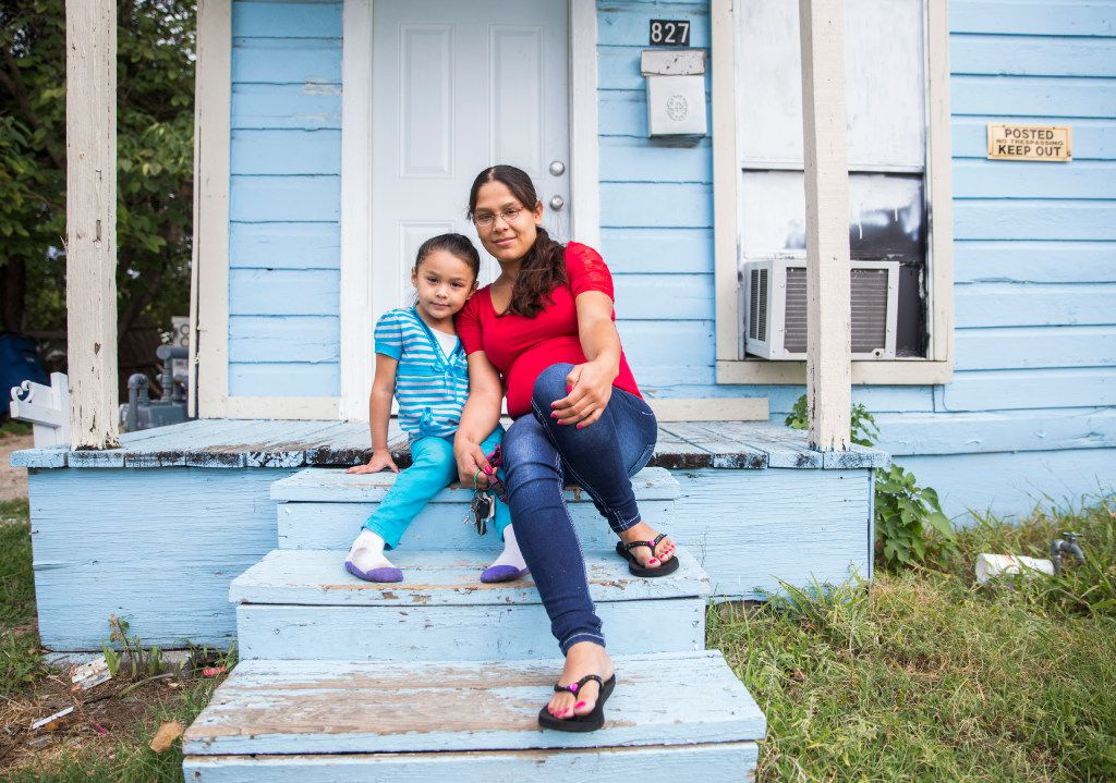 Joanna Pena poses with 4-year-old daughter Zaory Rendon on the steps of her rental house in the Los Altos neighborhood of West Dallas. Pena was the first tenant to sue in civil court over housing conditions provided by HMK Ltd., a low-rent landlord in Dallas (Ashley Landis/Staff Photographer)