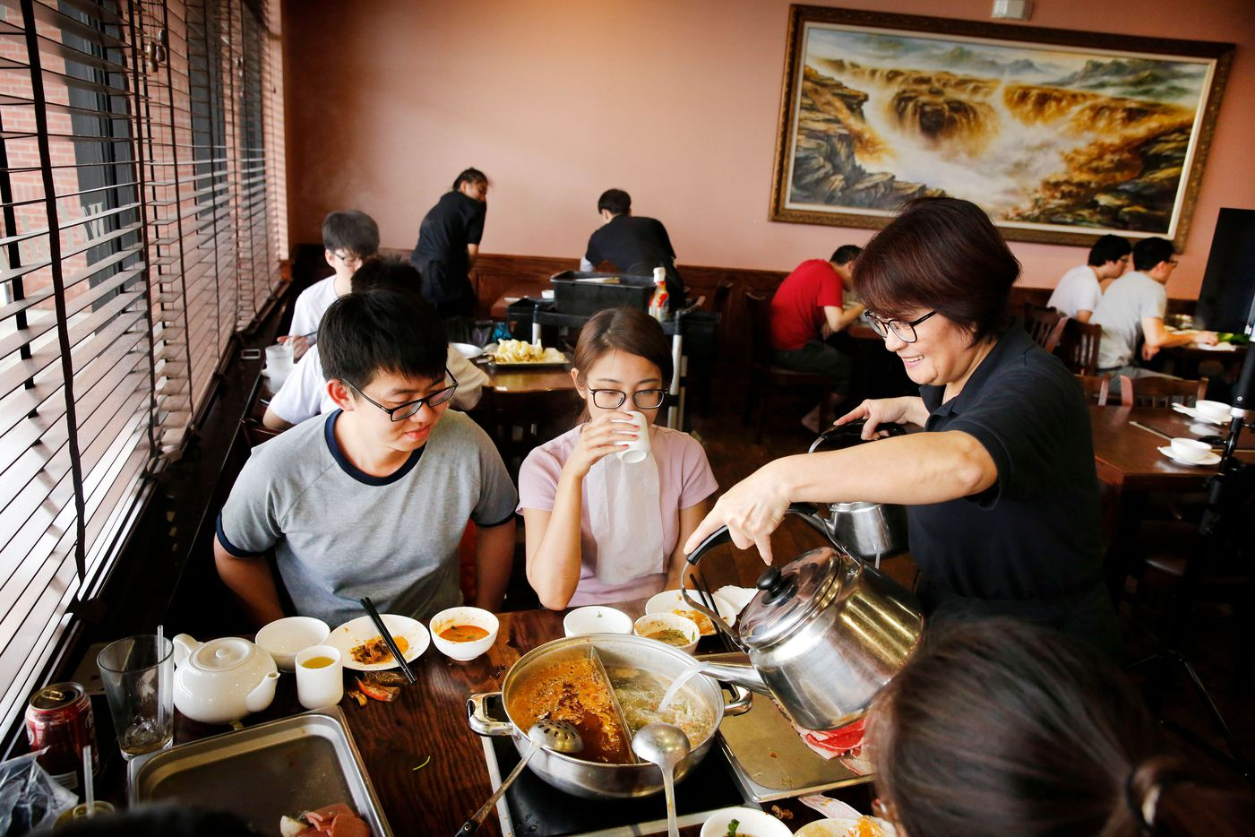 Server Jennifer Ke (right) adds liquid to the hot pot boiling at a table of young diners at Sichuan Folk in Plano. (Tom Fox/Staff Photographer)
