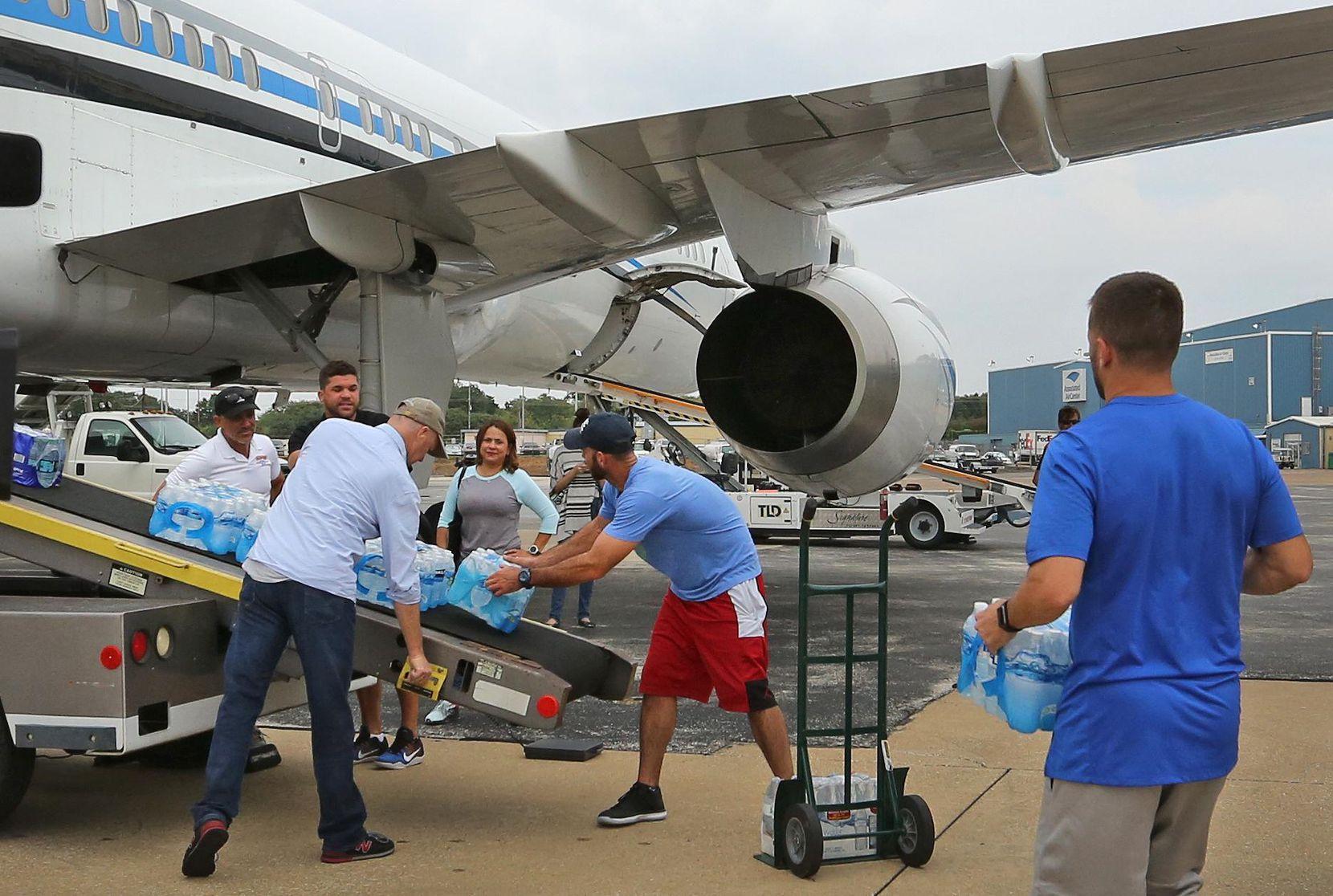 l jugador de los Mavericks, J.J. Barea (der.) ayuda a cargar de vituallas el avión de los Mavericks, en Love Field, para ser entregados en Puerto Rico. DMN