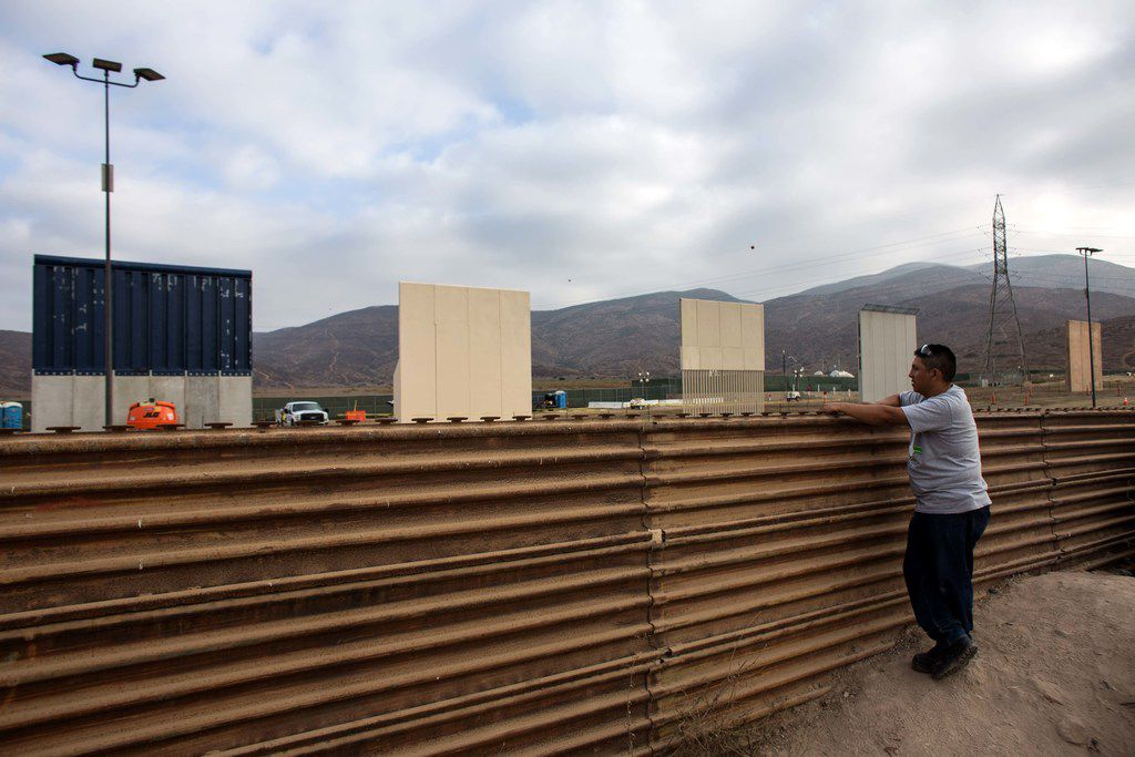 A man in Tijuana, Mexico, watches across the border as a prototype of President Donald Trump's border wall is built near San Diego on Oct. 12.