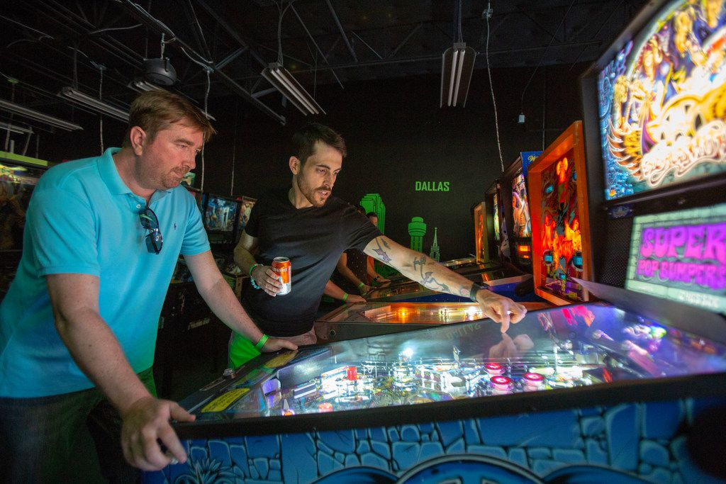 Jimmy Williams (left) and Elijah Riess (right) play an Aerosmith pinball machine during the grand opening of Regeneration Arcade Bar and Pizzeria in Dallas, Texas, Friday, August 17, 2018.