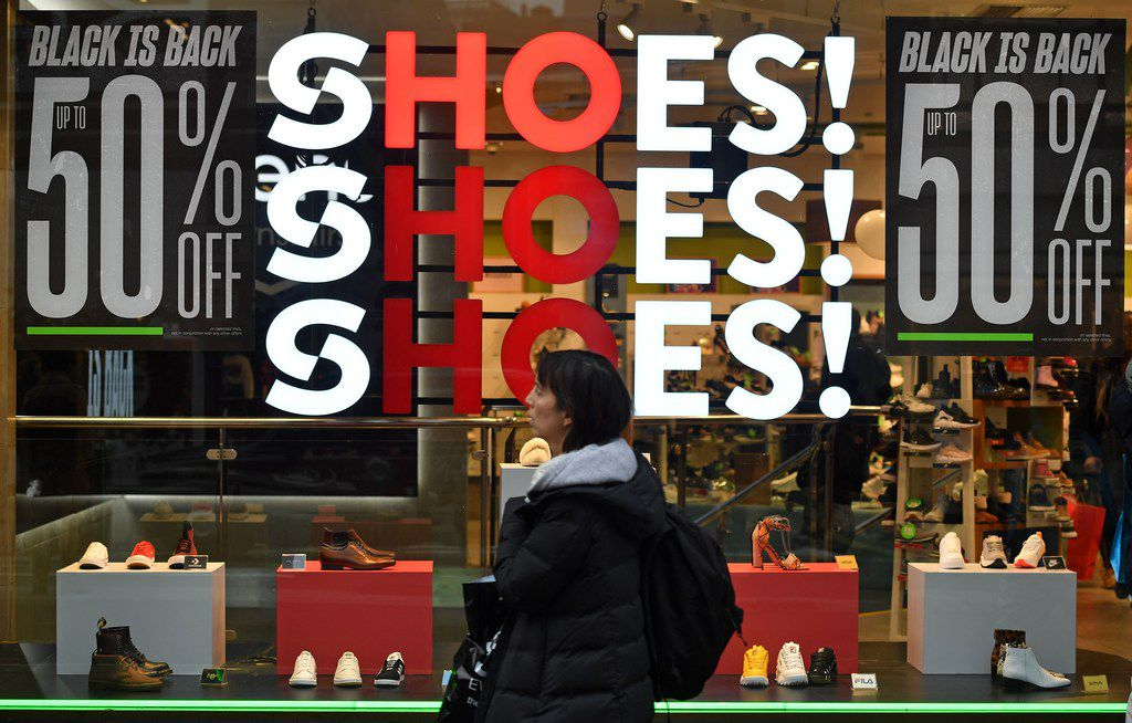 Shoppers pass a promotional sign for 'Black Friday' sales discounts in London, on November 23, 2018. - Black Friday is a sales offer originating from the US where retailers slash prices on the day after the Thanksgiving holiday. In the UK it is used as a marketing device to entice Christmas shoppers with the discounts at stores often lasting for a week. (Photo by Ben STANSALL / AFP)BEN STANSALL/AFP/Getty Images