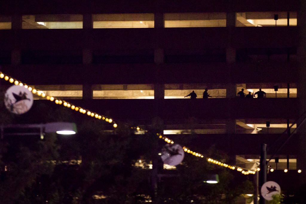 Silhouettes of law enforcement officers are seen in a parking garage at Lamar and Main during a standoff between police and the gunman after shots were fired during a Black Lives Matter rally in Dallas on Thursday.  As the rally and march were winding down, Micah Xavier Johnson, 25, opened fire in an attack that killed five police officers.