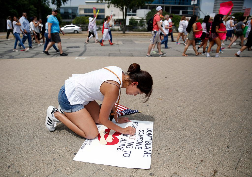 Lily Schmitt of Allen uses a tube of lipstick to finish her protest sign Saturday.