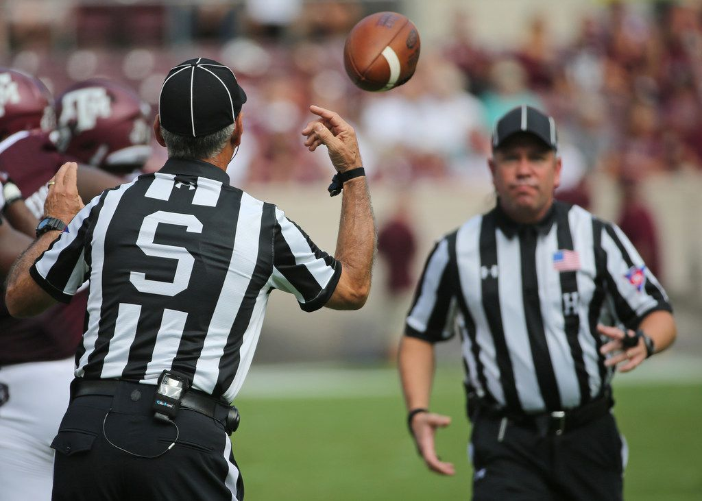 Side Judge Bobby Moreau tosses a game ball to Head Linesman Tim Sistrunk during the  Louisiana Lafayette Ragin' Cajuns vs. the Texas A&M Aggies at Kyle Field in College Stadium, Texas on Saturday, September 15, 2017. (Louis DeLuca/The Dallas Morning News)