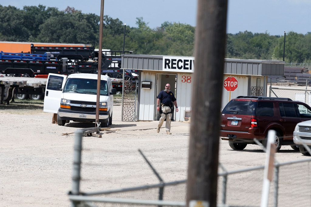 An ICE agent outside Load Trail LLC. after Immigration and Customs Enforcement raided the trailer manufacturer.