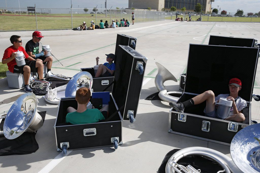 Band members get some shade in instrument boxes during marching band practice at Lebanon Trail High School.