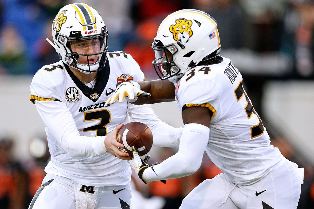 MEMPHIS, TENNESSEE - DECEMBER 31: Drew Lock #3 of the Missouri Tigers hands the ball to Larry Rountree III #34 during the first half of the AutoZone Liberty Bowl  against the Oklahoma State Cowboys at Liberty Bowl Memorial Stadium on December 31, 2018 in Memphis, Tennessee. (Photo by Jonathan Bachman/Getty Images)
