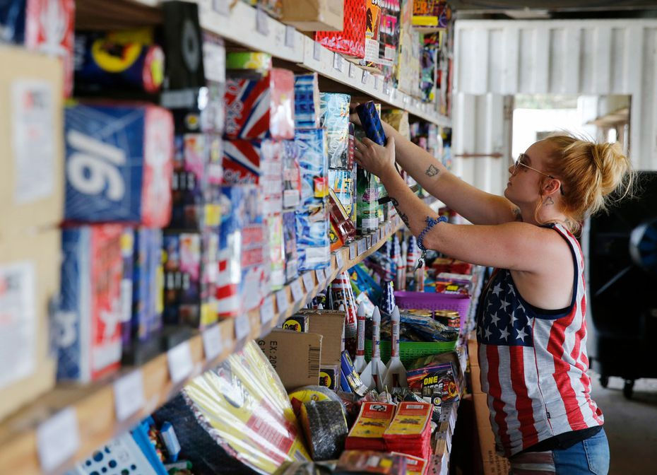 Dana Delgado restocks fireworks at Starr Fireworks in Kaufman County. Delgado has worked at the fireworks stand off and on for the past 10 years.